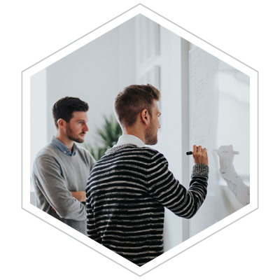 two male executives brainstorming on a whiteboard