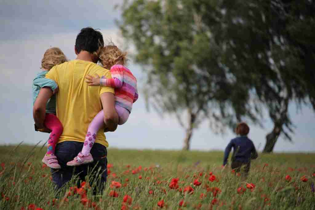 Parent carrying two children on hips walking through a field of flowers