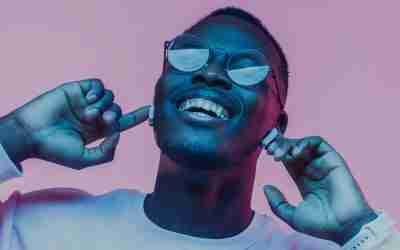 Young african man listening to music with earphones, dancing isolated on pink background
