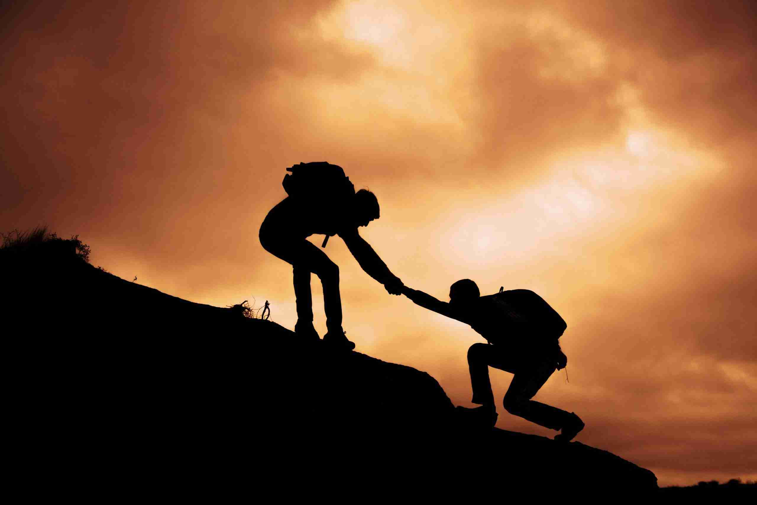 A person helping another person up a hill, signifying how critical it is to understand the challenges of the customer for customer experience.