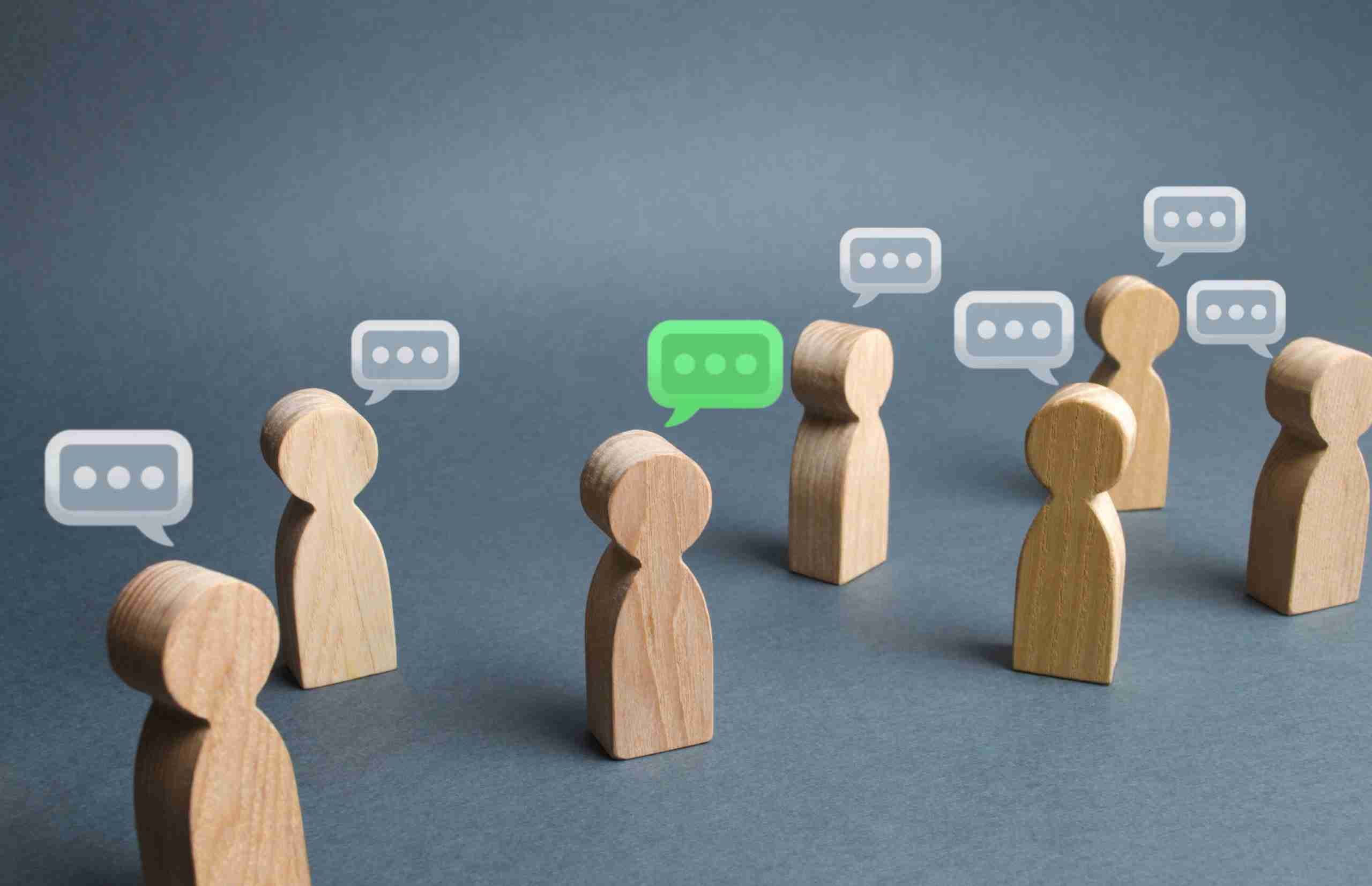 A group of human shaped wooden blocks signifying the diversity of employee experience in a company.